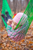 A girl lies in green hammock Stock Images