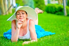 Girl lies on a green lawn Stock Image