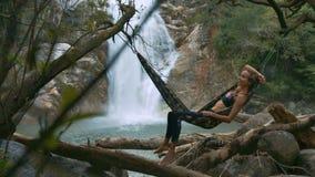 Girl Lies on Hammock above Stones Enjoys Leisure. Young girl lies on hammock tied to trees above stones and enjoys leisure against magnificent landscape stock video footage