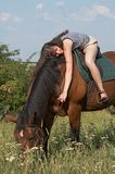 Girl lies on horseback Royalty Free Stock Photography