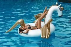 Girl lies on inflatable mattress. Tan girl lies on inflatable mattress white unicorn in the pool royalty free stock image