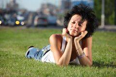 Girl lies on lawn at road in city Royalty Free Stock Photography