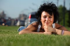 Girl lies on lawn at road in city Stock Photo
