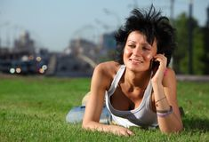 Girl lies on lawn at road and speaks by phone Royalty Free Stock Image