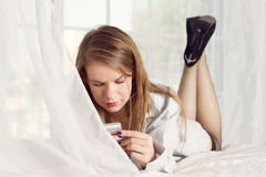 Girl lies in a man's shirt on the bed with Royalty Free Stock Photo
