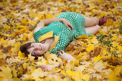 Girl lies in maple leaves Royalty Free Stock Photography