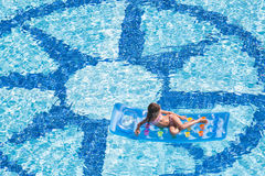 A girl lies on mattress in the pool Royalty Free Stock Image