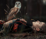 Girl lies with owl on grass in forest. Close-up. Stock Photos