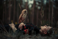 Girl lies with owl on grass in forest. Stock Image