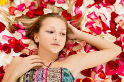 Girl lies in the petals of roses Royalty Free Stock Image