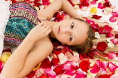 Girl lies in the petals of roses Stock Photography