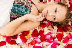 Girl lies in the petals of roses Royalty Free Stock Images