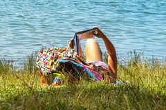 A girl lies in a river and reads a book. Young woman reading a book while sitting by the river royalty free stock photo