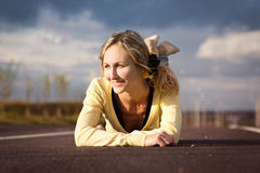 The girl lies on road. Looks aside and smiles Stock Photos