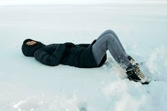 The girl lies in the snow stock photography