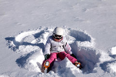 Girl lies on snow. Snow angel Royalty Free Stock Photo