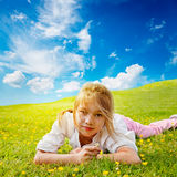 Girl lies in sunny meadow Stock Photos