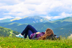 Girl lies on top of the mountain Stock Images