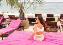 Girl lies on a tropical beach on pink sun loungers royalty free stock photos