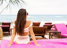 Girl lies on a tropical beach on pink sun loungers stock photography