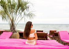 Girl lies on a tropical beach on pink sun loungers royalty free stock image
