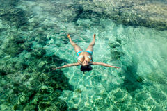 The girl lies on the turquoise waters on the Sunny sea coast Stock Photos
