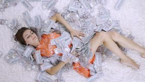 Girl lies on a white bed in lot of money. The girl enjoys lot of money. slow motion. Huge wealth of money.  stock video
