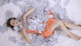 Girl lies on a white bed in lot of money. The girl enjoys lot of money. slow motion. Huge wealth of money.  stock video footage