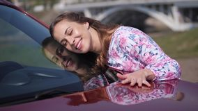 The girl lies on the windshield, gently smiles and strokes the car. 4K Slow Mo stock video