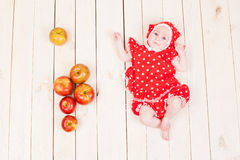 Girl lies on a wooden floor and apples Royalty Free Stock Photography