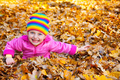 Girl lies on yellow leaves in autumn park Stock Photo