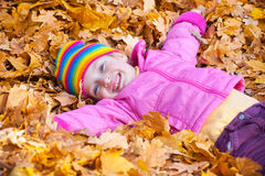 Girl lies on yellow leaves in autumn park Royalty Free Stock Photos