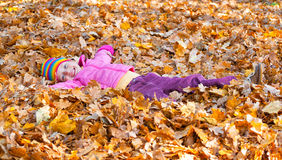 Girl lies on yellow leaves in autumn park Royalty Free Stock Image