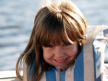 Girl in Life Preserver. A young girl with a big smile on a boat Stock Photo