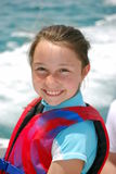 Girl with life vest. Smiling girl wearing a life vest in a boat in the Bahamas royalty free stock image