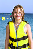 Girl with life vest at the beach. Smiling girl with life vest at the beach royalty free stock photography