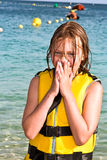 Girl with life vest at the beach. Smiling girl with life vest at the beach royalty free stock images