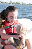 Girl with Lifejacket. Little girl wearing an orange lifevest holding her teddy bear Stock Images
