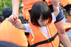 Girl with lifejacket. Little girls in lifejackets walking to the boat stock photos