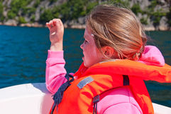 The girl in a lifejacket sitting in a boat Stock Images