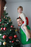 Girl lift in the fathers shoulders next to the Christmas tree Royalty Free Stock Image