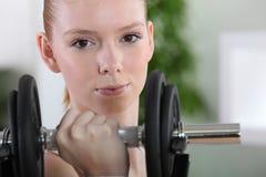 Girl lifting dumbbell Stock Image