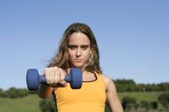 Girl lifting dumbbells Stock Image