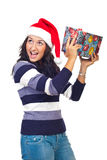 Girl lifting a gift and listen to what's inside Stock Photo