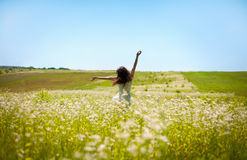 Girl lifting her hands up in the air runs across the field.  Royalty Free Stock Photography