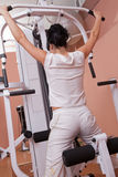 Girl lifting weight on gym apparatus. Pretty brunette girl lifting weight on gym apparatus Stock Photography