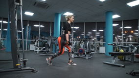 The girl lifts dumbbells. Blonde is engaged in sports with sports equipment stock video