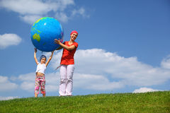 Girl lifts an globe upwards and mother helps stock image