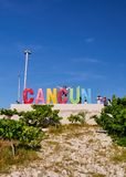 Girl lifts her arms up in Cancun sign stock photography