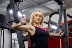 Girl lifts weights in gym on a butterfly machine Stock Photos